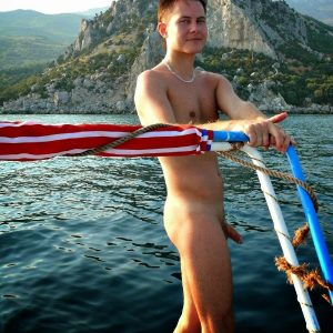 Cute nudist boy on a boat