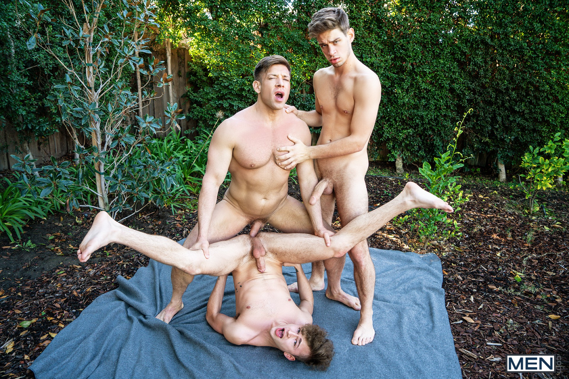 Gay men having a threesome outdoors